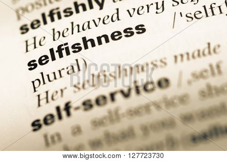 Close Up Of Old English Dictionary Page With Word Selfishness.
