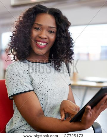Casual portrait of an african american business woman using technology in a bright and sunny startup with windows in the background