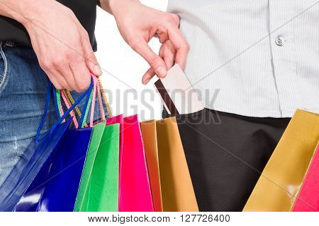 Shopping woman taking credit card from man's pants pocket on white background