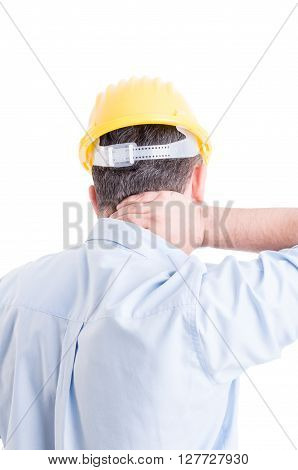 Tired engineer suffering from back neck pain and wearing blue shirt and yellow helmet