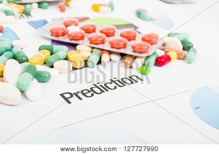 Pills sales prediction concept with printed graphs and bunch of pills