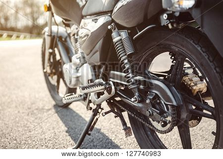 Close up shock absorber, chain and disk brake of black shiny motorcycle