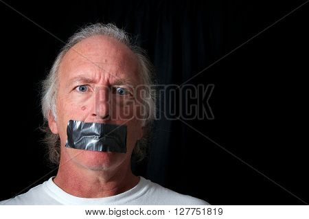 Studio portrait of an older blue eyed man with mouth duct taped closed looking distraught black background with copy space. Political correctness or freedom of speech concept.