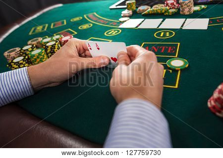 Male poker player holding the of two cards aces at green casino table