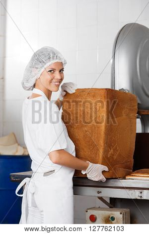 Confident Baker With Bread Loaf Standing At Table
