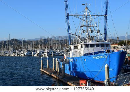 April 20, 2016 in Ventura, CA:  Commercial Fishing Vessel which is used to catch deep sea fish in the Pacific Ocean with sail boats and yachts docked beyond at the Ventura Harbor where people can rent boats and travel on their own boats taken in Ventura,