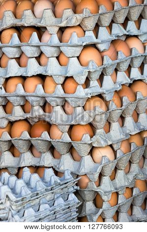 dozens of eggs in cartons in an assortment of colors stacked at the market