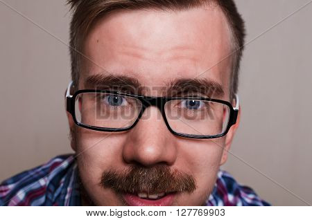 Close up portrait of hipster. kind person wath into camera. Big face with glasses and beard poster