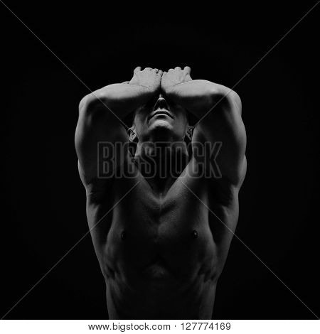 Athletic young shirtless muscular man on black