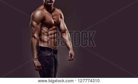 Athletic young shirtless muscular man in jeans