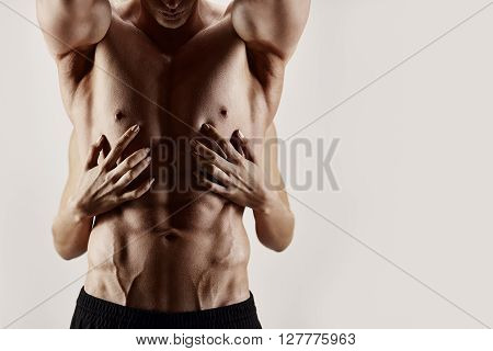 Female's hands holding muscular torso on white