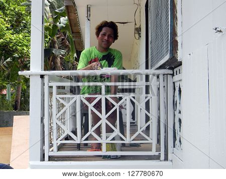 MABINI, SOUTHERN LEYTE / PHILIPPINES - AUGUST 5, 2011: A painter paints the railing of a balcony of a home in the village of Mabini.
