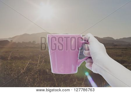 Woman hand holding coffee cup with sunrise, stock photo