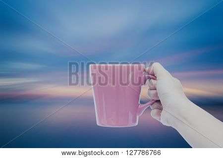 Woman hand holding coffee cup with sunset blur background, stock photo