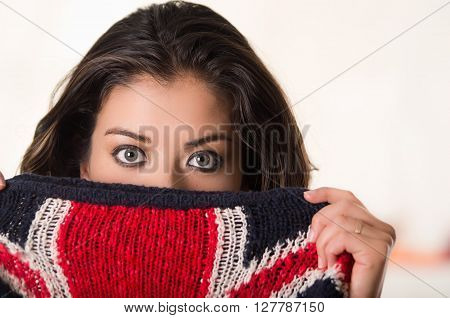 Headshot attractive brunette facing camera covering half her face with british flag patterned clothing, white studio background.