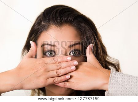 Headshot attractive brunette facing camera covering half her face using both hands, white studio background.