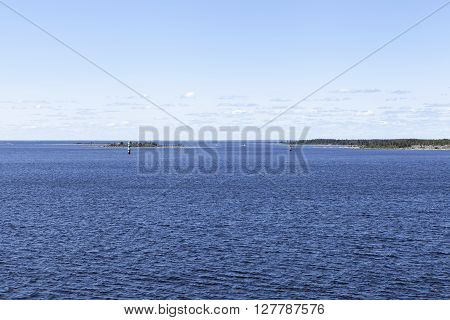 Coast and coastline up North in the Baltic Sea. Islands, rocks and the mainland, continent. Windmills in the background. Beacon this side. ** Note: Shallow depth of field
