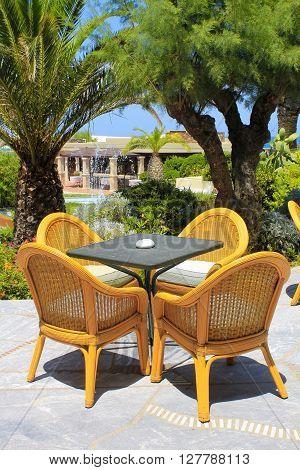 Al fresco terrace wicker chairs and palm trees in the mediterranean hotel, Crete, Greece