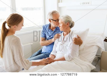 medicine, support, family health care and people concept - senior man and young woman visiting and cheering her ill grandmother at hospital ward poster