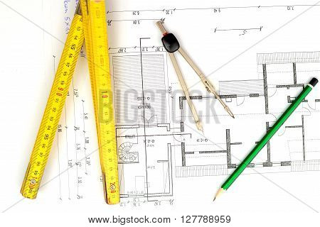 building plan with pencil folding yardstick and compass on wooden table