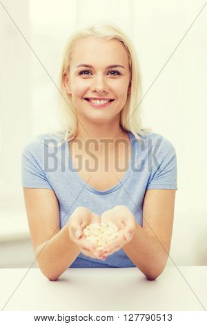 healthy eating, medicine, health care, food supplements and people concept - happy woman holding pills or capsules at home