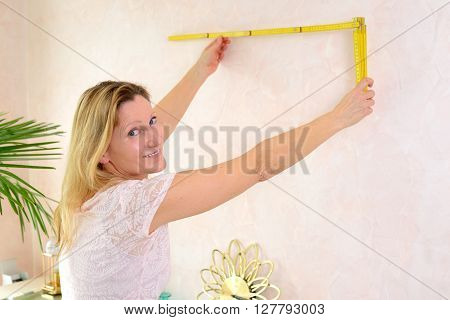 Woman Redecorate Home And Working With Folding Yardstick