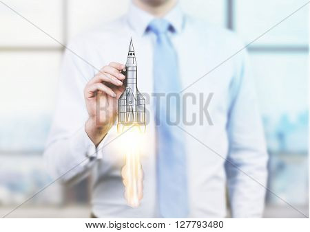 Start up concept with businessman holding rocket ship miniature