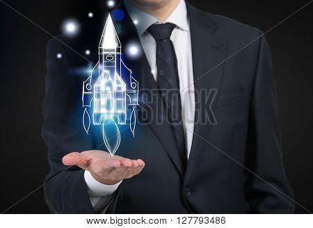 Start up concept with businessperson holding digital rocket on dark background