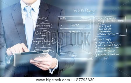 Web design plan with businessman using tablet on blue background