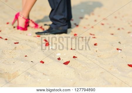 Legs of young hugging or kissing couple standing on sand beach. Pretty rose petal strewn on the sand. Girl in red shoes a man in trousers. Wedding ceremony on the beach.
