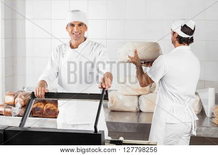 Male Baker Using Vacuum Seal Machine In Bakery