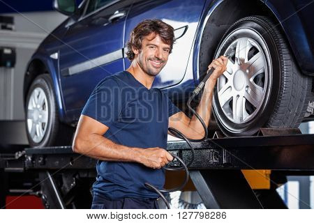 Happy Mechanic Filling Air Into Car Tire At Garage