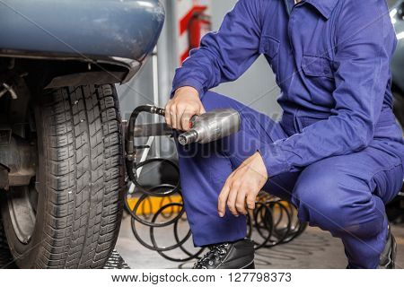 Mechanic Holding Pneumatic Wrench By Car