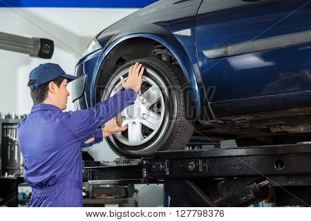 Mechanic Fixing Alloy To Car Tire