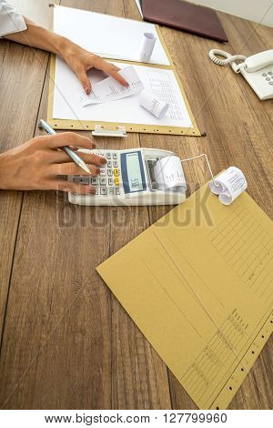 Finance and accounting concept - closeup of office desk with paperwork documents and data and female hands using calculator and holding printout receipt.