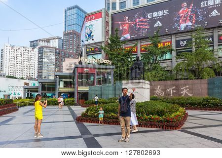 Chengdu China - August 15 2015 - Tourists taking photo in front of the sculpture of Sun Yat-sen at the Zhongshan Square on Chunxi Road in the downtown of Chengdu Capital city of Sichuan Province in China.