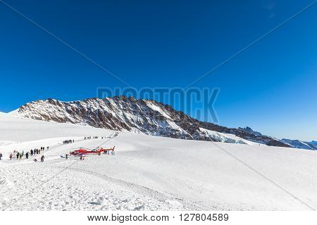 Jungfraujoch Switzerland - December 28 2015 - Tourists on the winter hiking pass outside the Jungfraujoch railway station with view of Trugberg and The Aletsch glacier.