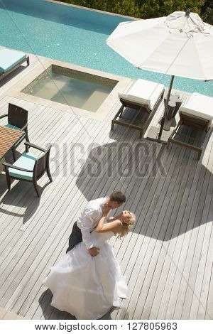 Lovely, Gorgeous Couple Kissing Close To Pool Area After Wedding.