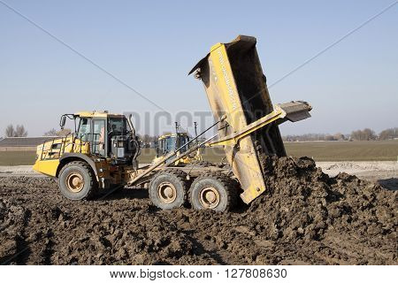 Grootebroek , the netherlands - 17 march , 2016: Big yellow articulated dumper fixes a load of excavated clay