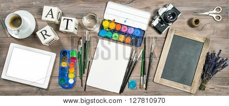 Artistic workplace. Watercolor brushes digital tablet pc chalkboard vintage no name camera office supplies tolls and accessories