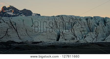 Ice-blue offshoots of a glacier tonngue in front of mountains in Iceland
