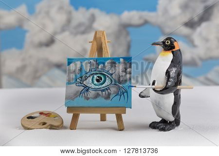 Model of a penguin painting a surrealist fish with eye and sky scene