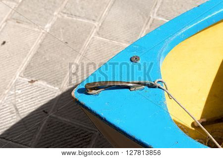 Detail of a wooden blue prow of a rowing boat moored on pier. Liguria Italy