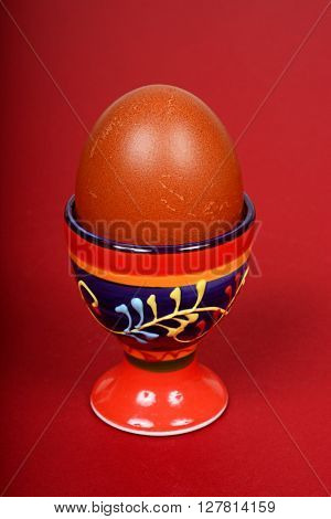 A boiled egg in a decorative ceramic eggcup against a red background.