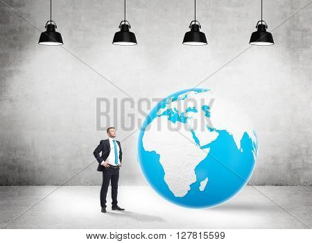 Global business concept with businessman standing in concrete interior with huge terrestrial globe and sever.