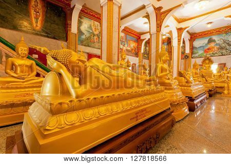 PHUKET, THAILAND - FEB 6, 2016: Sleeping Buddha statue and other inside hall of famous Wat Chalong on February 6, 2016. First written mention about the buddhist monastery belongs to 1837