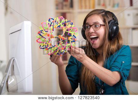 Brunette woman sitting by desk holding up molecular model kit and smiling.