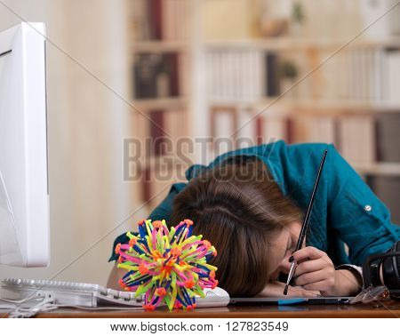Brunette woman sleeping at desk with computer and molecular model kit on table.