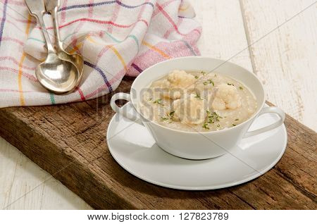 cauliflower soup with thyme in a bowl on rustic brown wood