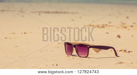 Sun glasses lie on a beach near sea